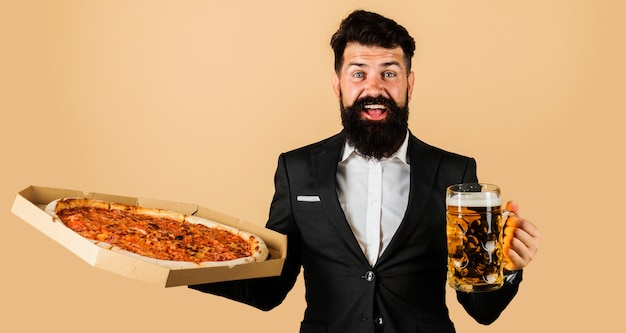 レストランまたはピッツェリア。ピザとビールを手に笑顔の男。イタリア料理。ピザの宅配。