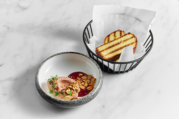 Restaurant pate with berry sauce, peanuts and microgrin in a marble plate with toast in a metal basket on a white marble background
