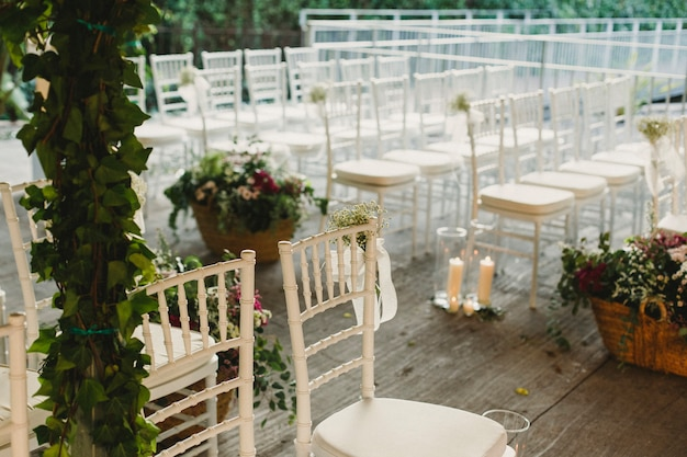 A restaurant prepares a wooden platform to place vintage chairs and create a retro atmosphere for a wedding ceremony.