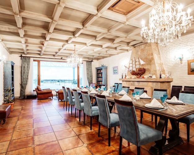 파란 의자, 흰 벽, 벽난로 및 넓은 창문이있는 식당 개인 실 _
