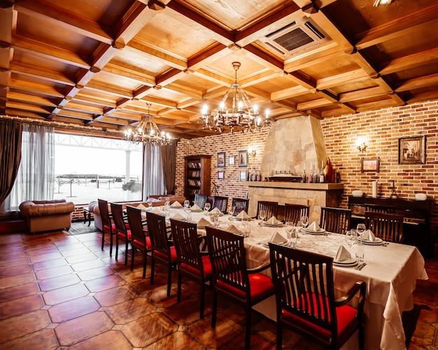Отдельная комната ресторана со столом на 14 персон, деревянным потолком, кирпичными стенами и камином