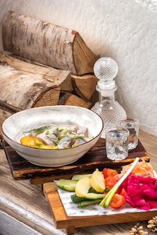Ресторан seafood menu с соленой сельдью с луковыми кольцами и вареной нарезанной кубиками картошкой на элегантной ресторанной тарелке с набором алкогольной холодной водки и ассорти из маринованных.