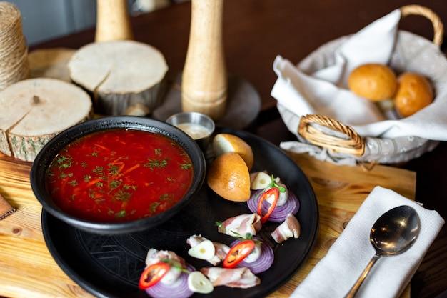 コショウと木製の背景にベーコンの前菜と黒い皿にウクライナのボルシチのレストランサーブ