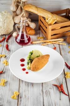 В ресторане подается котлета из курицы по-киевски с картофельным пюре и брусничным соусом.