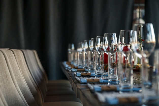 Restaurant serving and glass wine and water glasses, forks and knives on textile napkins stand in a row on gray wooden table.