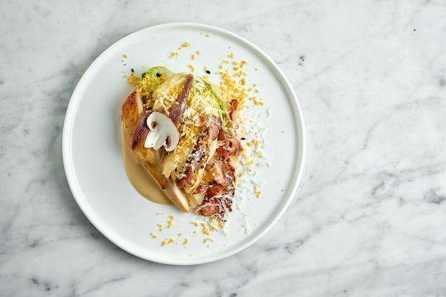 Ресторанная подача классического салата цезарь с гренками, яйцом, грибами, курицей-гриль, пармезаном и беконом подается в белой тарелке на мраморном столе.