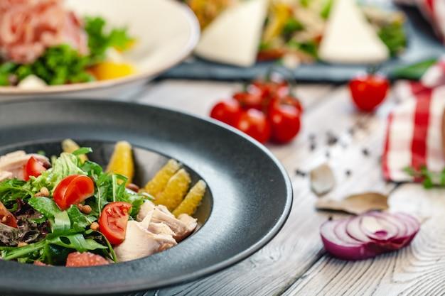 Restaurant starter menu of veggie salad with meat slices
