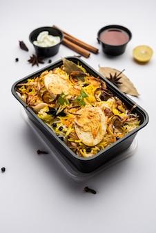 レストランスタイルのエッグビリヤニまたはアンダプラオは、ライタとサランが入ったプラスチックの箱または容器に宅配用に梱包されています