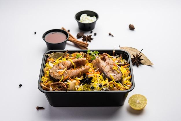 レストランスタイルのフィッシュビリヤニまたはプラオは、ライタとサランが入ったプラスチックの箱またはコンテナに宅配用に梱包されています