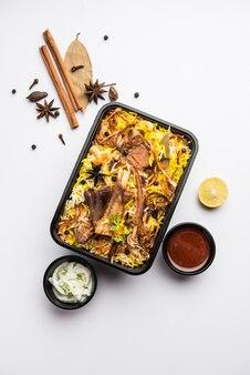 Ресторанный стиль gosht или mutton biryani или pulao, упакованный для доставки на дом в пластиковой коробке или контейнере с raita и salan.