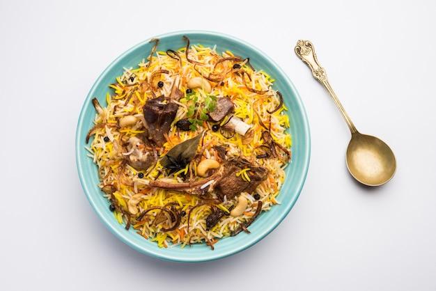 Ресторанный стиль gosht или mutton biryani подается в миске с raita и саланом. Premium Фотографии