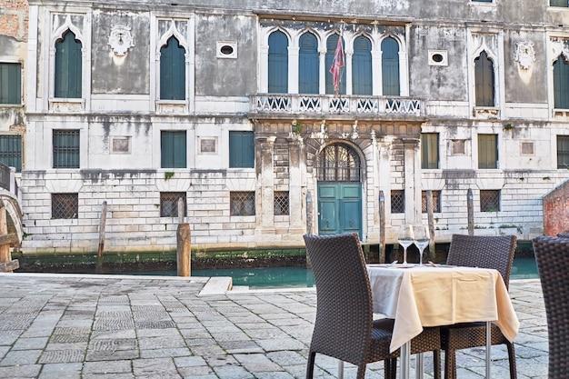 イタリア、ベニスの運河近くのレストランのテーブル。