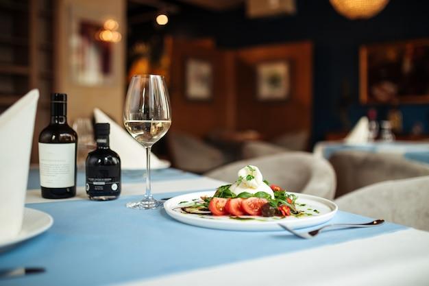 야채와 채소를 곁들인 미식가 스페인 부라 타 샐러드와 함께 제공되는 레스토랑 테이블
