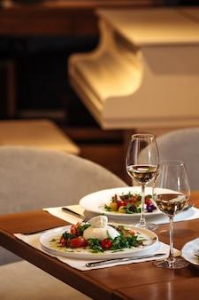 サラダと白ワインのグラスを添えたレストランのテーブル