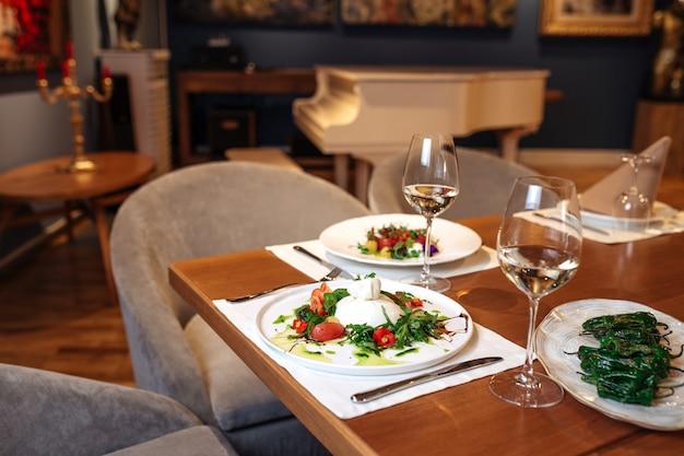 스페인 식 부라 타 토마토와 페퍼 샐러드를 곁들인 레스토랑 테이블