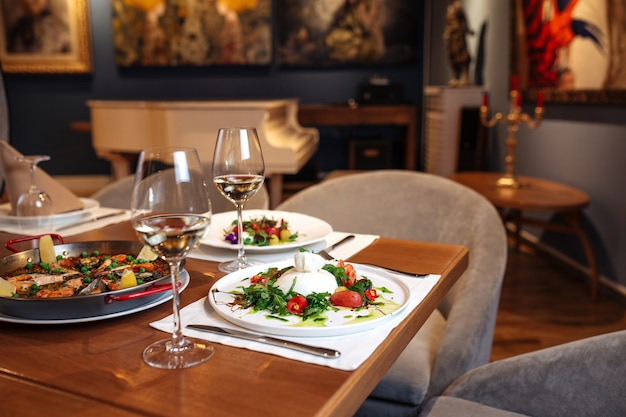 Restaurant table served with spanish buratta tomato and peppers salads and paella