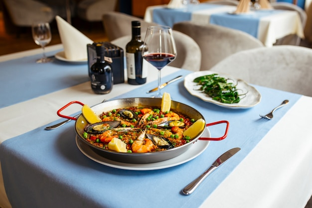 Restaurant table served with spanish dishes seafood paella and padron peppers