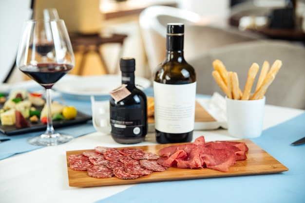 Restaurant table served with spanish jamon and smoked sausage on the wooden board