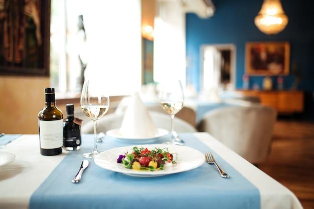 Стол в ресторане с салатом из очищенных помидоров