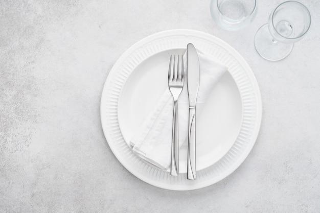 흰 접시, 유리 잔, 수저가있는 레스토랑 테이블 세팅