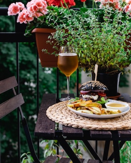 Restaurant table on terrace with hamburger from black bun