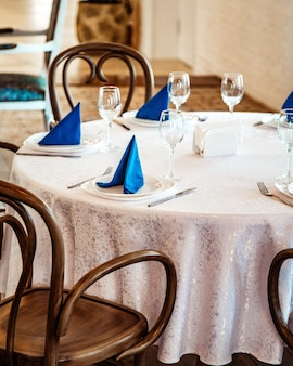 Restaurant table with white lace table cloth and blue napkins