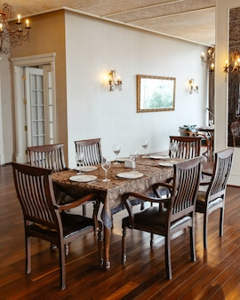 Restaurant table with wooden chairs placed in hall decorated in classical style
