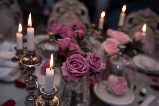 A restaurant. a vase of pink roses is on the table. a romantic place.
