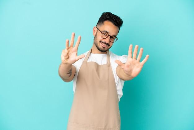 Ресторан официант кавказский человек изолирован на синем фоне, считая девять пальцами