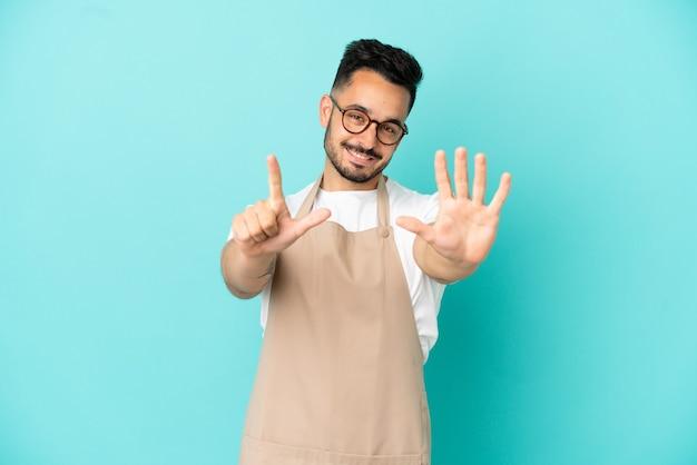 Ресторан официант кавказский человек изолирован на синем фоне, считая семь пальцами
