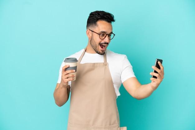 Ресторан официант кавказский человек изолирован на синем фоне держит кофе на вынос и мобильный