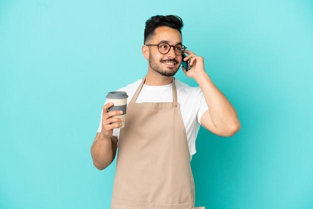 파란색 배경에 격리된 레스토랑 웨이터 백인 남자는 테이크아웃 커피와 모바일을 들고 있습니다.