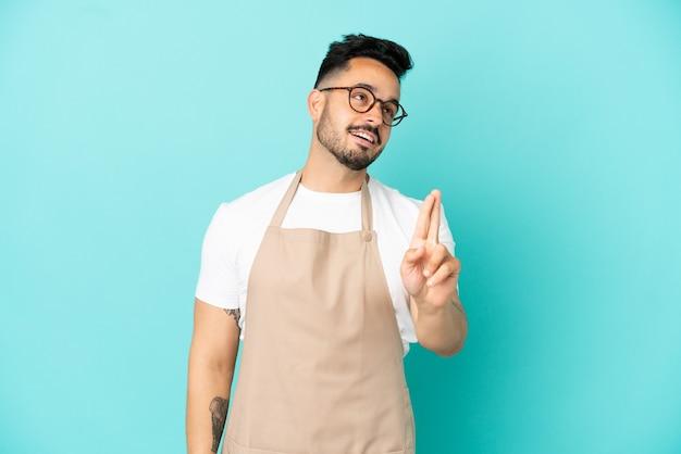 Официант ресторана кавказский человек изолирован на синем фоне со скрещенными пальцами и желает лучшего
