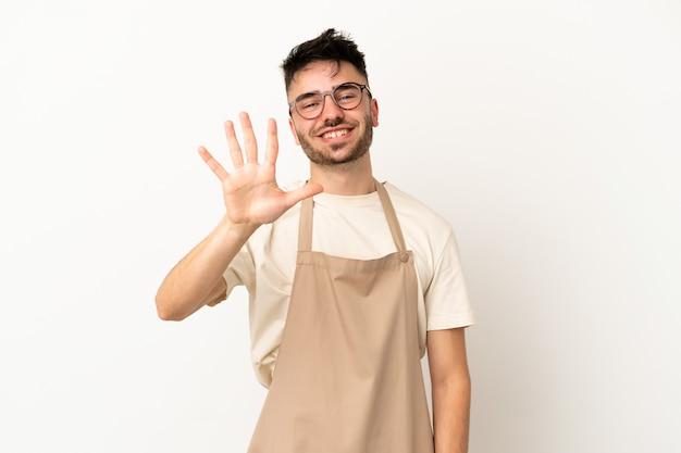 Ресторан официант кавказский человек изолирован на белом фоне, считая пять пальцами