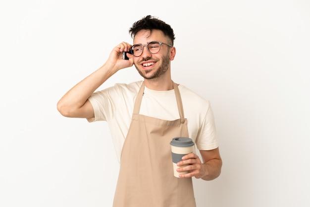 持ち帰り用のコーヒーと携帯電話を保持している白い背景で隔離のレストランウェイター白人男性