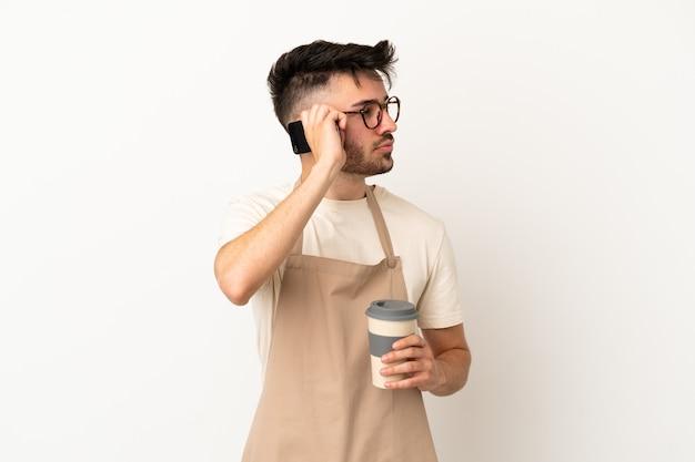 Ресторан официант кавказский человек, изолированные на белом фоне, держа кофе на вынос и мобильный