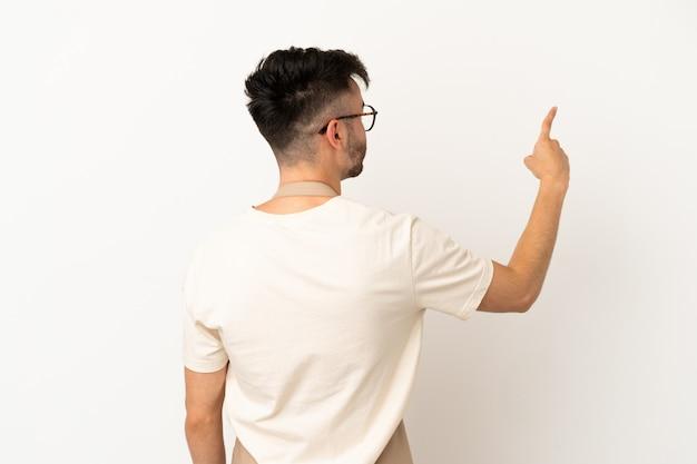 人差し指で後ろ向きの白い背景で隔離のレストランウェイター白人男性