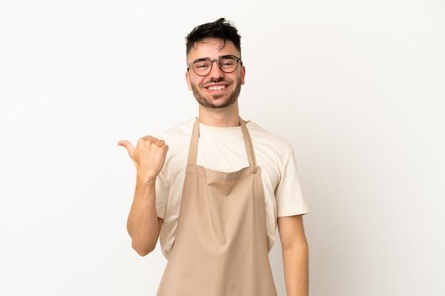 Ресторан официант кавказский человек, изолированные на белом фоне, указывая в сторону, чтобы представить продукт