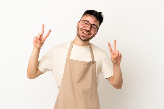 Ресторан официант кавказский человек изолирован на белом фоне показывает знак победы обеими руками