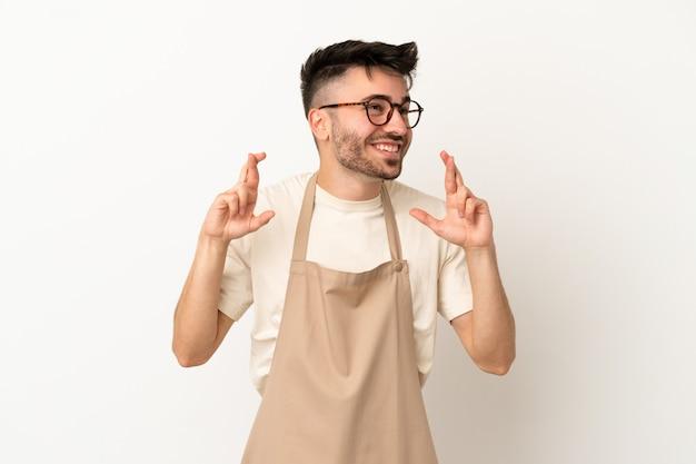 Ресторан официант кавказский человек, изолированные на белом фоне со скрещенными пальцами