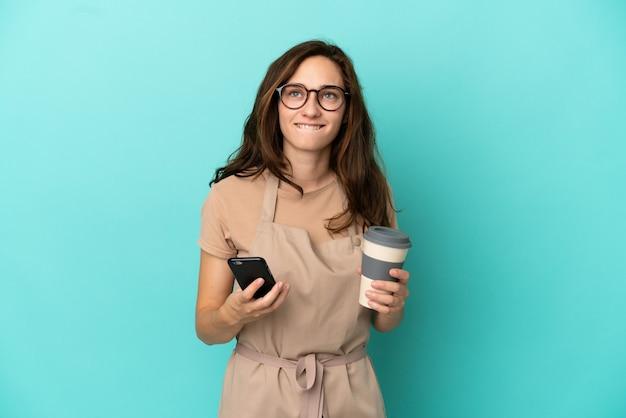 テイクアウトするコーヒーと何かを考えながら携帯を持っているレストランのウェイター