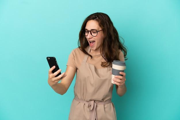 Официант ресторана держит кофе на вынос и мобильный