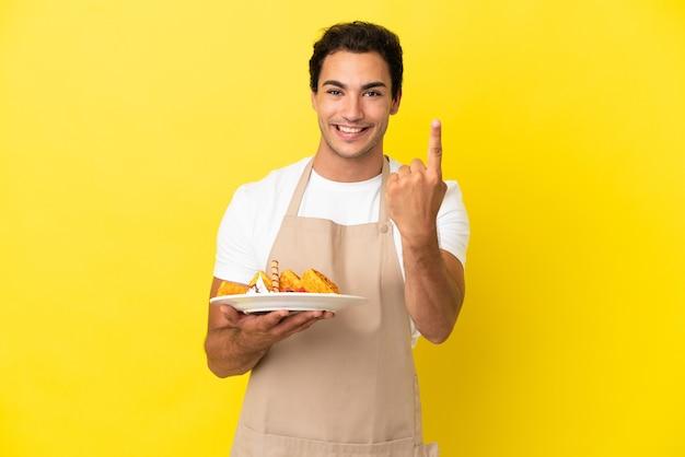 Официант ресторана держит вафли на изолированном желтом фоне, делая приближающийся жест
