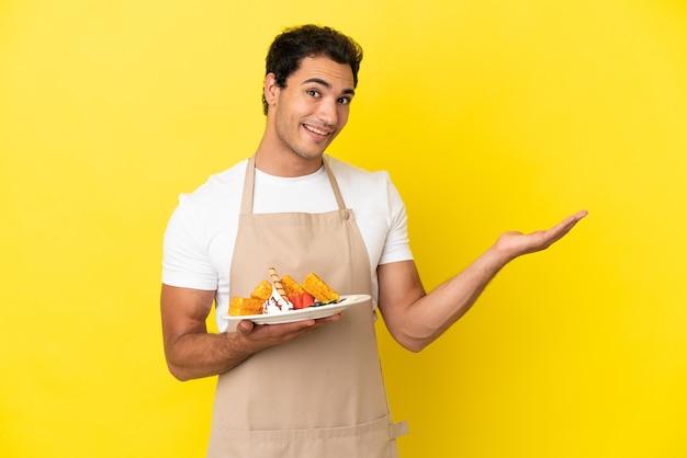 孤立した黄色の背景の上にワッフルを持ってレストランのウェイターが手を横に伸ばして招待します
