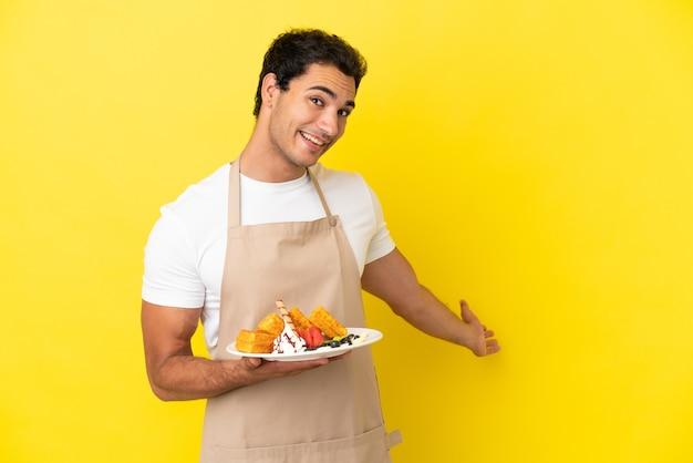 Официант ресторана держит вафли на изолированном желтом фоне, протягивая руки в сторону, приглашая прийти