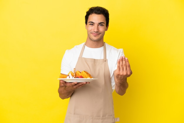 고립된 노란색 배경 위에 와플을 들고 있는 레스토랑 웨이터가 손을 잡고 초대합니다. 당신이 와서 행복