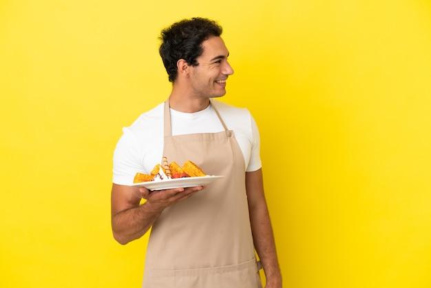 Официант ресторана держит вафли на изолированном желтом фоне, смотрит в сторону и улыбается