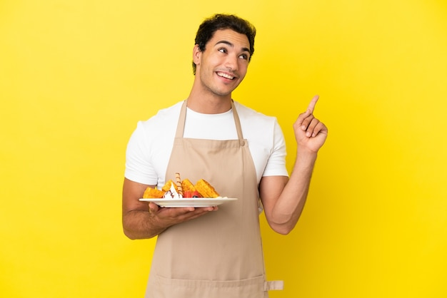 Официант ресторана держит вафли на изолированном желтом фоне, указывая на отличную идею