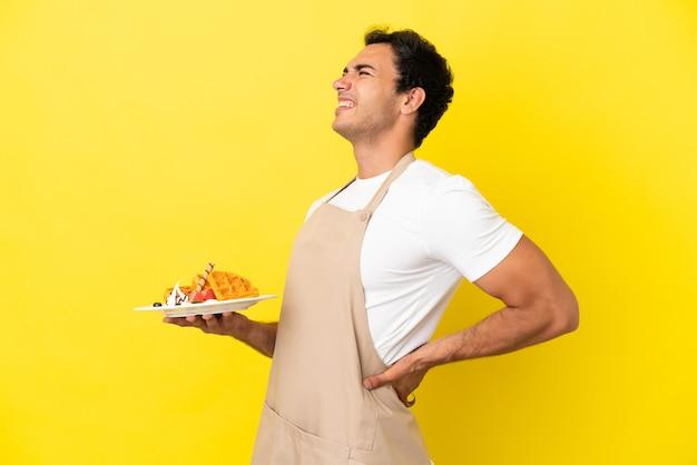 Официант ресторана держит вафли на изолированном желтом фоне и страдает от боли в спине из-за того, что приложил усилия