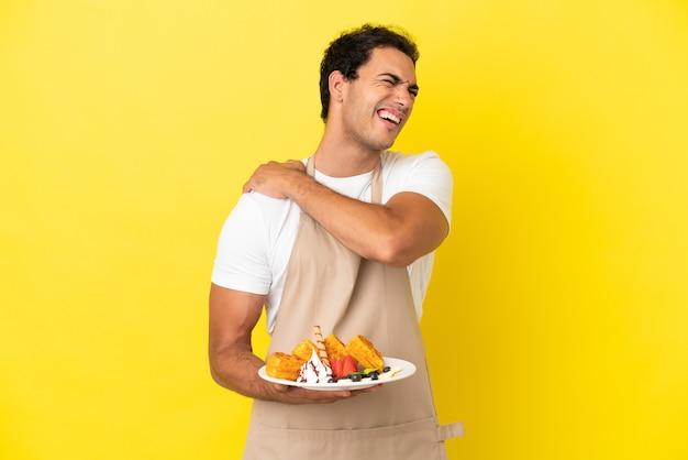 Официант ресторана держит вафли на изолированном желтом фоне и страдает от боли в плече за то, что приложил усилие